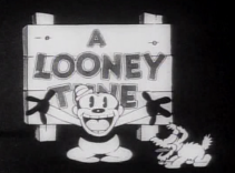 Bosko and a dog are standing in front of a wooden sign that says Looney Tunes, Bosko's hands are raised